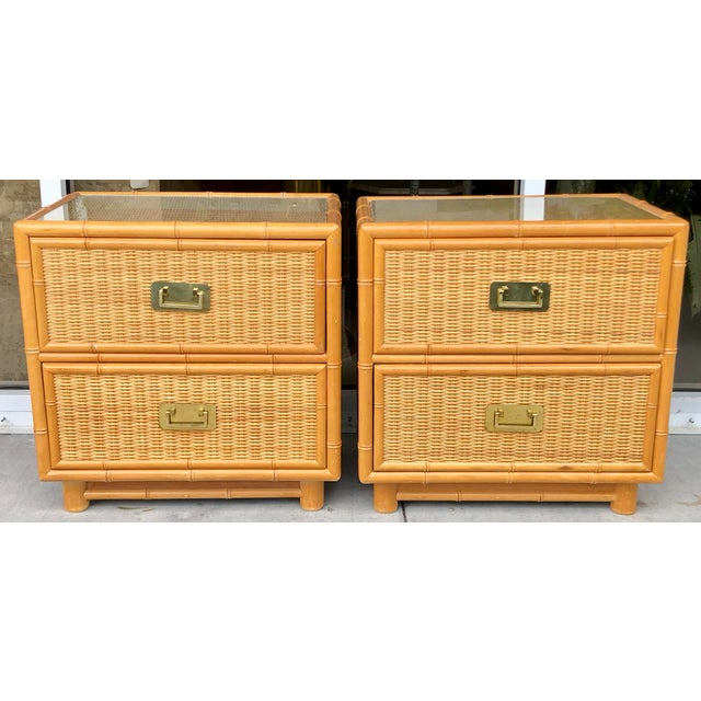 Set of two classic coastal style nightstands. Wood Structure covered with bamboo and rattan. Glass tops and sleek solid...