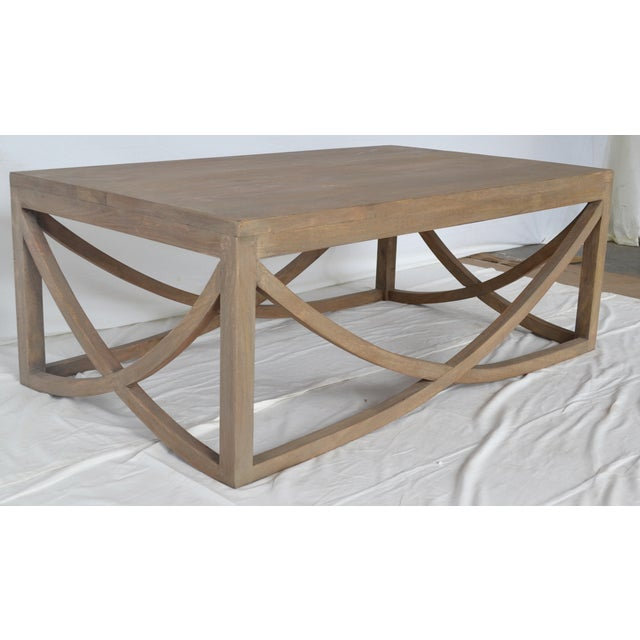 Offered is a contemporary coffee table crafted from distressed mango wood and featuring a hand applied finish. Minor...