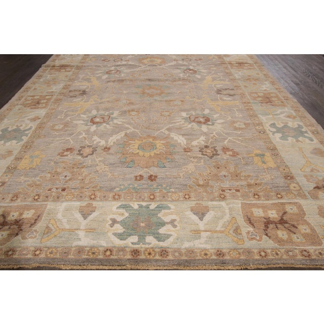 A hand-knotted Sultanabad rug with a geometric design on a brown field. Accents of gray, green and blue throughout the piece.