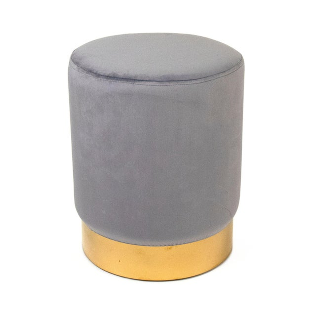 Cylindrical stool upholstered in pale blue velvet with stylish gold rim on bottom.
