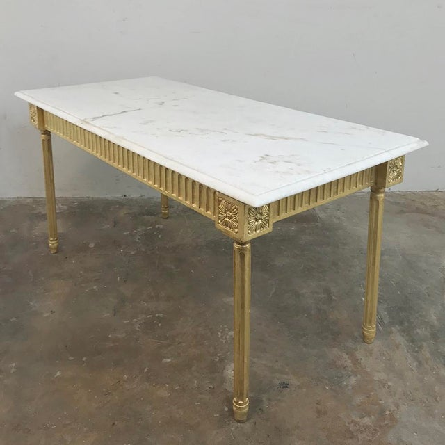 Antique French Louis XVI Gilded Marble Top Coffee Table was carved to perfection in the neoclassic style, with fluted...