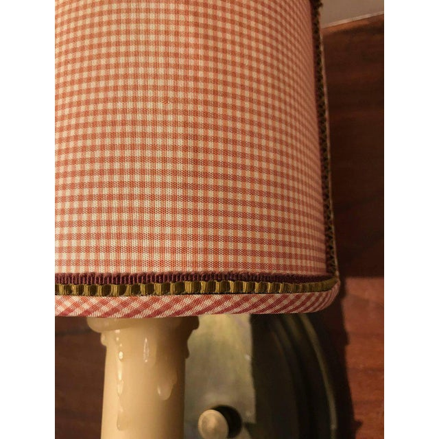 Trimmed gingham shades on brass sconces.