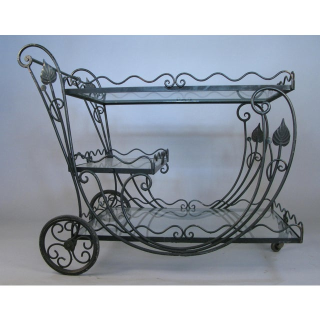 A beautiful vintage 1950s rolling bar cart by Woodard, with scrolled design around all the frames. The cart has three...