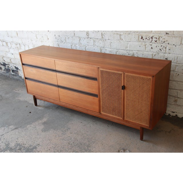 Offering a gorgeous mid-century modern walnut and cane dresser or credenza designed by Kipp Stewart for his American...