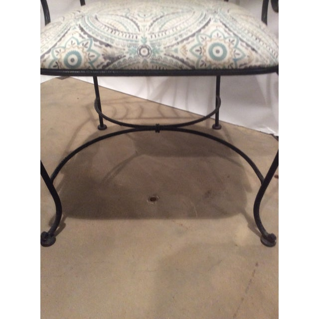 Pair of black wrought iron garden chairs with scrolling arm on cabriole legs and upholstered seat.