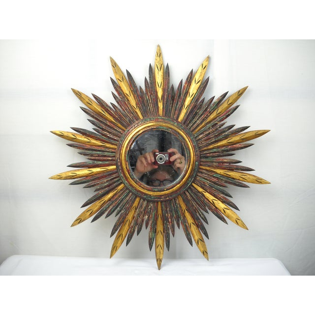 French carved wood starburst mirror with layered tones of brown, green, red, white and gilding. No maker's mark. Hanging...