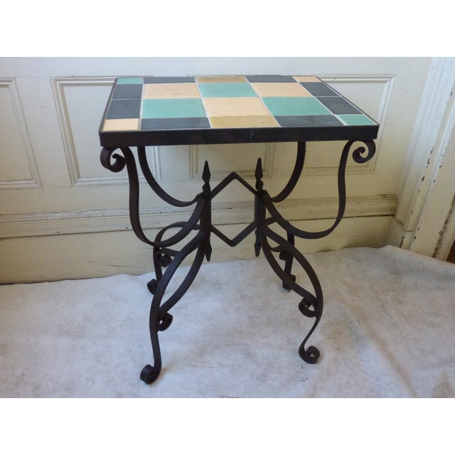 Mid-century heavy weight wrought iron base with multicolored inset ceramic tile.