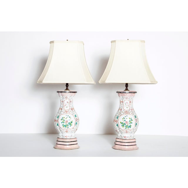 A pair of late 18th century Chinese vases as lamps with new shades. White porcelain bodies with applied floral designs....