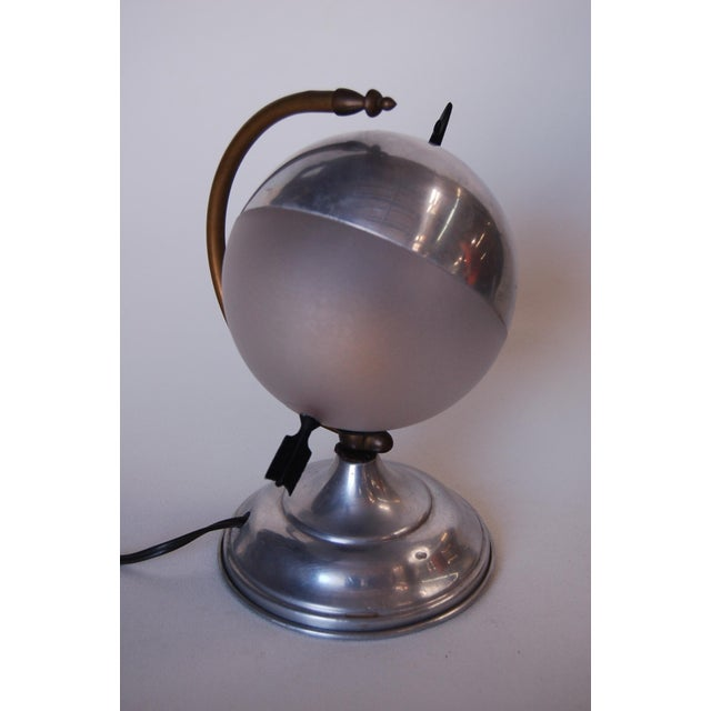 "Art Deco aluminum swivel globe hemisphere ""Saturn"" accent table lamp with brass arrow details. Measures 6""wide x 6.5"" deep..."