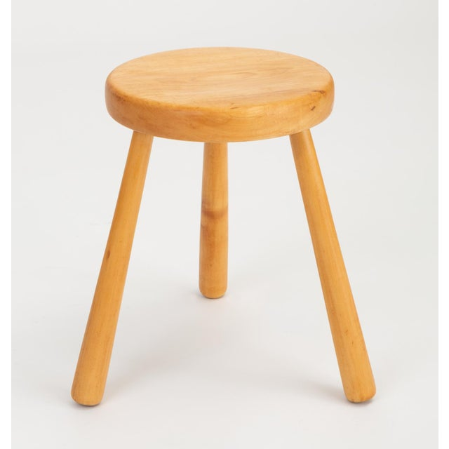 A small, three-legged stool in pine wood, similar to Charlotte Perriand's 1968 rustic modern designs for the Les Arcs ski...