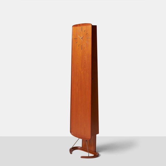 Hovmand-Olsen teak clock cabinet. Features a shallow cabinet with 5 interior shelves, half-moon shaped base with brass...