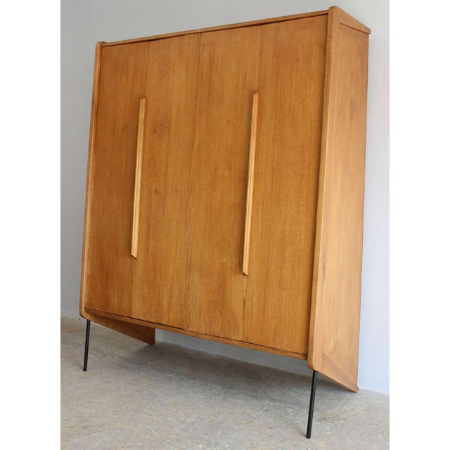 A handsome modern French beech wood wardrobe cabinet with interior shelves and hooks, design attributed to Claude Vassal.