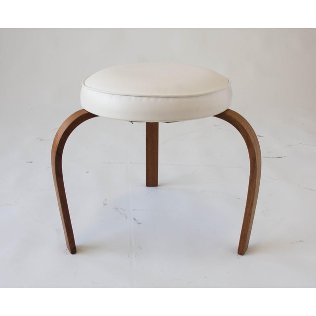 A modest stool after the designs of Alvar Aalto by Chicago-based manufacturer George Industries has a round cushion on...