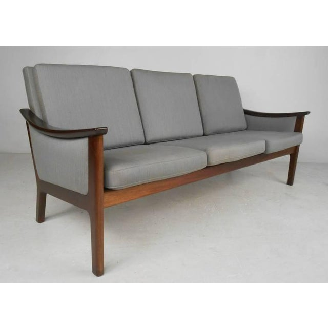 Sofa and two armchairs in the manner of ole wanscher. Graceful sloping rosewood arms with nicely detailed frames and...