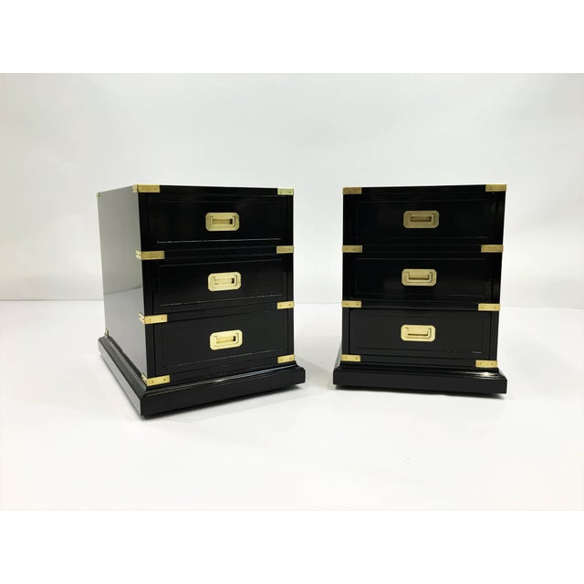 Elegant pair of lacquered Campaign style side tables. Richly adorned with gilt brass hardware and trim details, dovetailed...
