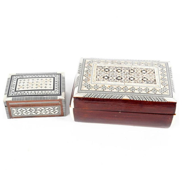 A pair of inlaid mother-of-pearl and wood jewelry boxes. The pair includes one larger and one smaller box, both made of...