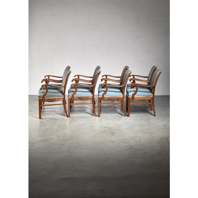 A set of twenty conference armchairs or dining chairs by Fritz Hansen, with a grey blue fabric upholstery. The chairs have...