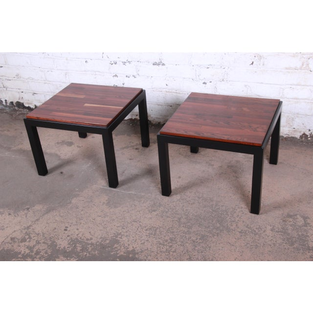 A sleek and stylish minimalist pair of mid-century modern walnut and ebonized wood square occasional side tables By Milo...