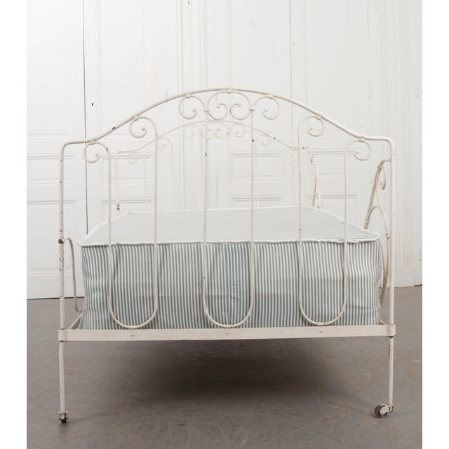 This lovely twin plus-size folding crème piente and gold-highlighted iron campaign daybed, c. 1890, was found in France....