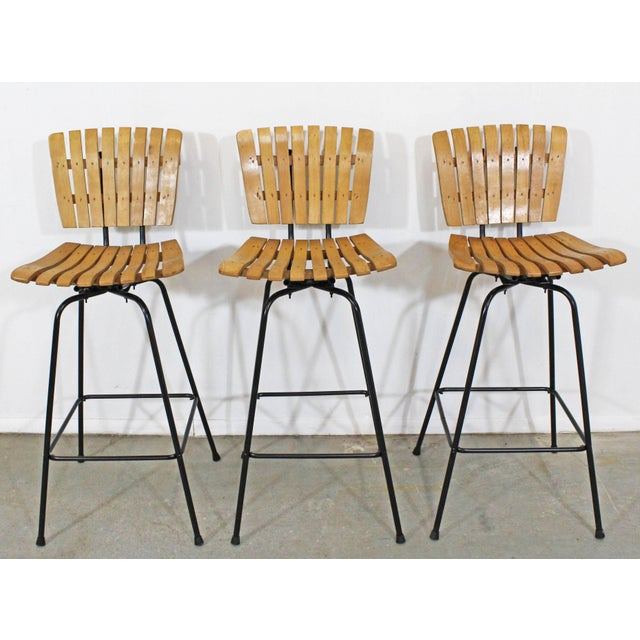 Offered is a set of 3 Umanoff-style slat bar stools that swivel. The stools are in good condition for their age, showing...