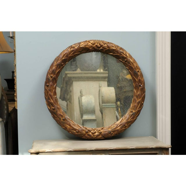 The Garland gilded wood circular mirror. This handmade circular Venetian style mirror features a gilded wood garland motif...