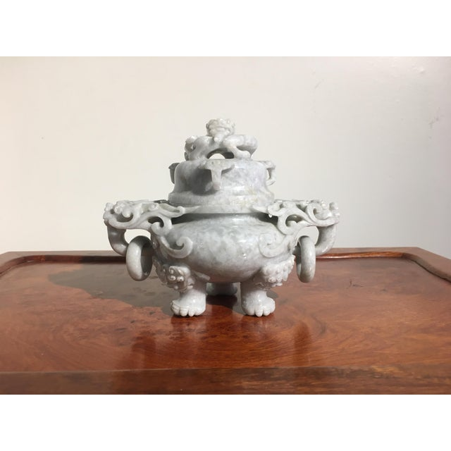 A lovely Chinese carved nephrite jade censer, set on three legs with lion masks and paws. The pair of handles of mythical...