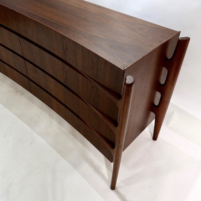 Exposed carved walnut legs with a curved bookmatched walnut front. Beautiful and sculptural eight drawer dresser designed...