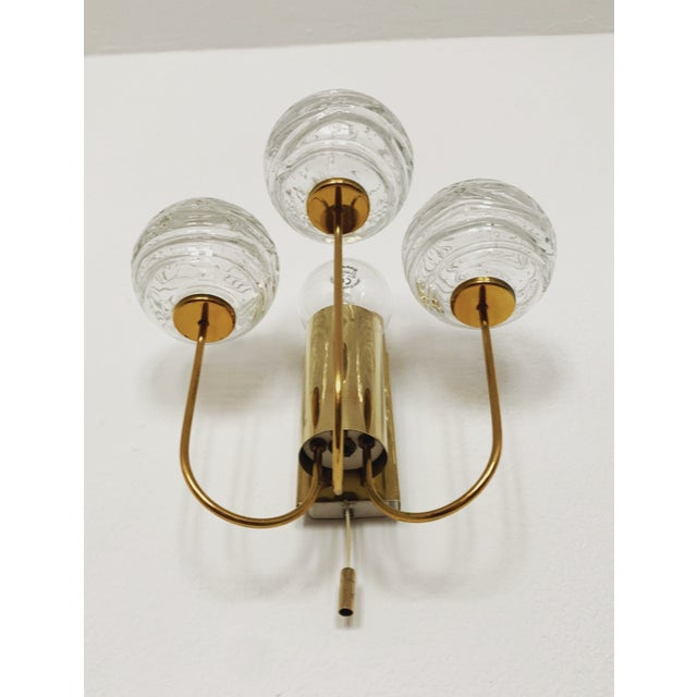 Rare ice glass and brass wall lamps from the 1950s made by Doria. The structured glass creates a wonderful sparkling light.