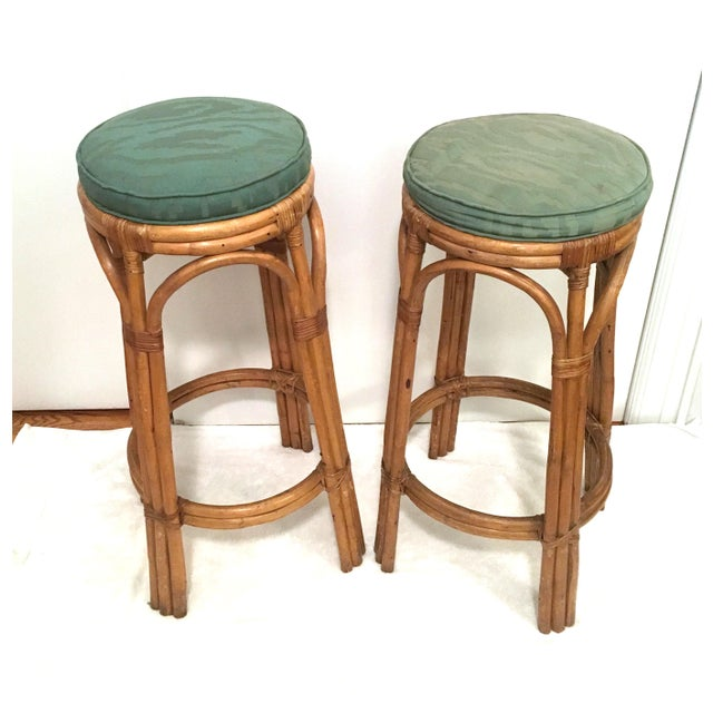 Pair of vintage rattan bar stools or plant stands. The rattan is in excellent condition and sturdy. The cushions we can...
