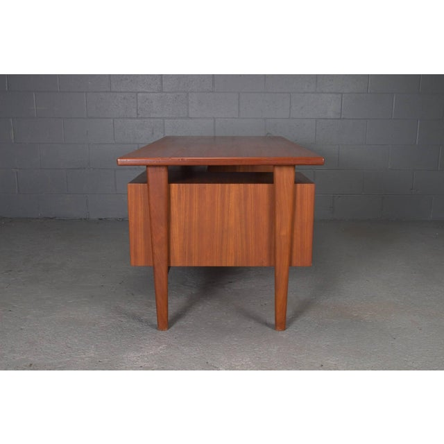 Danish teak desk with floating top by Kai Kristensen. Three open cubbies on opposite side. This executive desk is Model FM...