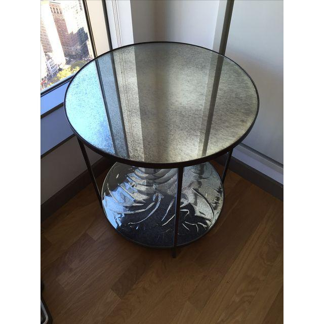 Beautiful antiqued mirrored two-tiered table. Features a cast iron frame. In perfect condition except the foil below the...