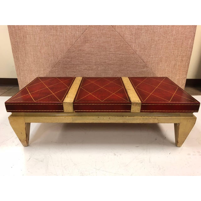 Mid-century modern leather top coffee table in the style of Tommi Parzinger. Tooled leather top with a bleached mahogany...