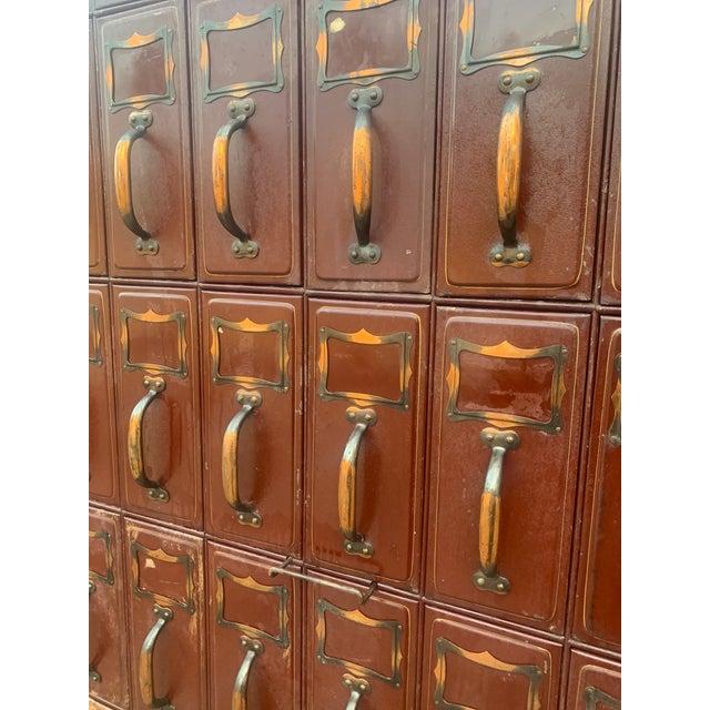 Vintage Industrial Filing Cabinet A Large Vintage Red metal courthouse ledger file cabinet with 56 drawers arranged...