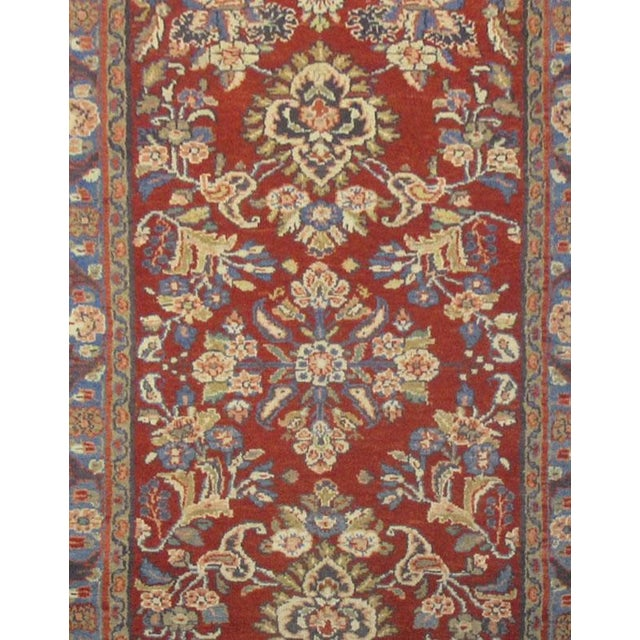 This beautiful rug is hand made, made in Iran. It features a pattern in a vibrant combination of red, navy blue, purple....