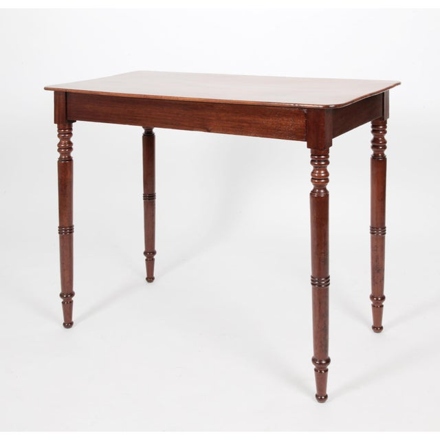 An antique English Regency mahogany side table, the attractively faded single board top over a darker base with turned...