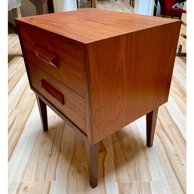 1960s Danish Modern teak nightstand with two drawers. The piece features rosewood detailing on the front and sculpted...