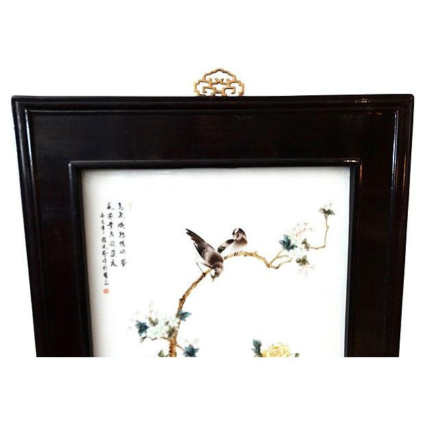 Hand-painted porcelain panel with birds, flowers, and trees. Displayed in a dark brown rosewood frame with iron hangers....