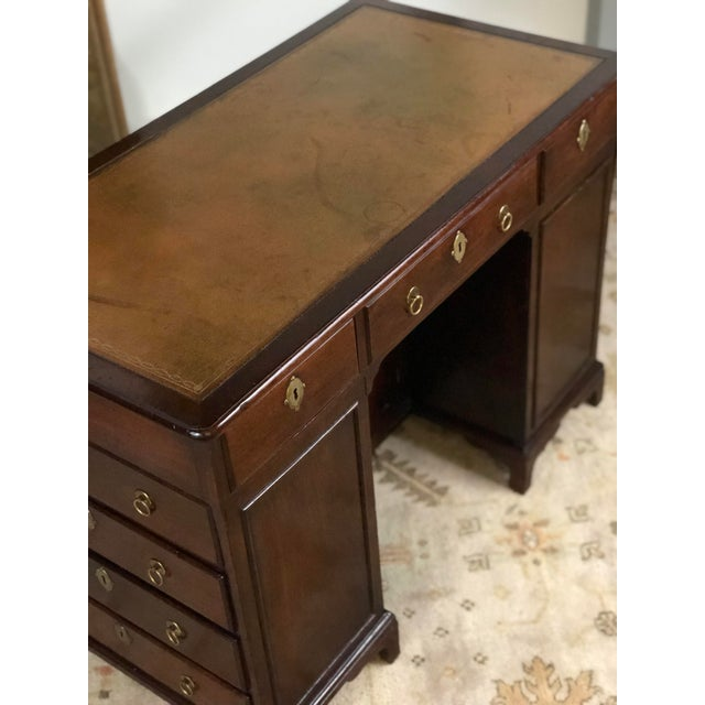 19th century English kneehole desk of mahogany created in the Regency style. The writing surface has an inset camel...