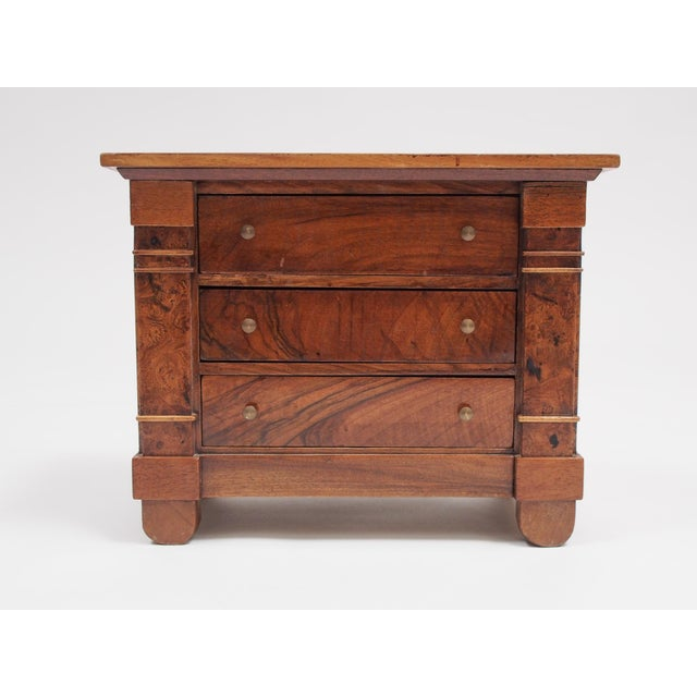A three drawer miniature commode, the drawers flanked with columns with rounded feet. Beautiful figured wood with a lovely...