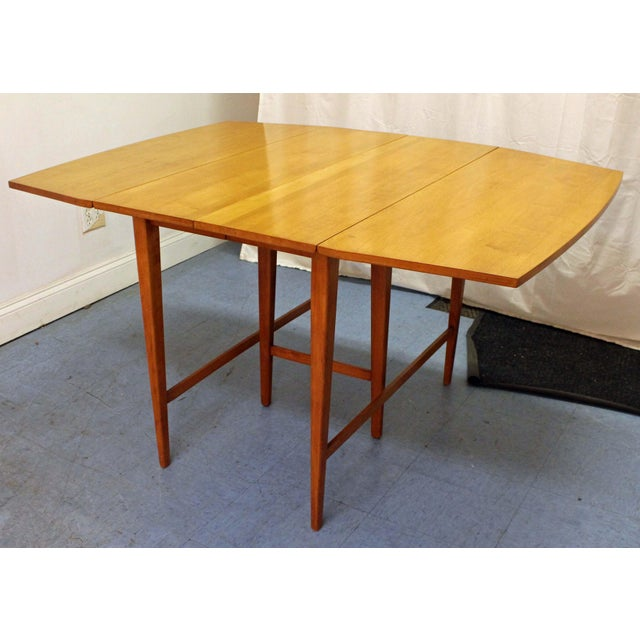 Offered is an extendable drop leaf dining table designed by Paul McCobb for Planner Group. This table is made of maple...