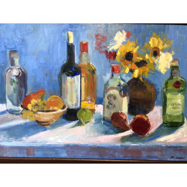 Vibrant still life with fruit, flowers, wine and liquor bottles arranged on a table, signed M. Goode in a wood frame.