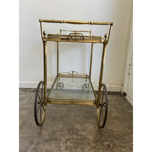 Vintage brass and glass bar cart with a removable tray top tray and fixed bottle holders on top and bottom. Charming...