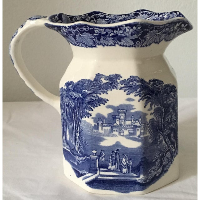 This blue and white transferware jug is decorated with figures dressed in 18th century costume on the ground of a castle....