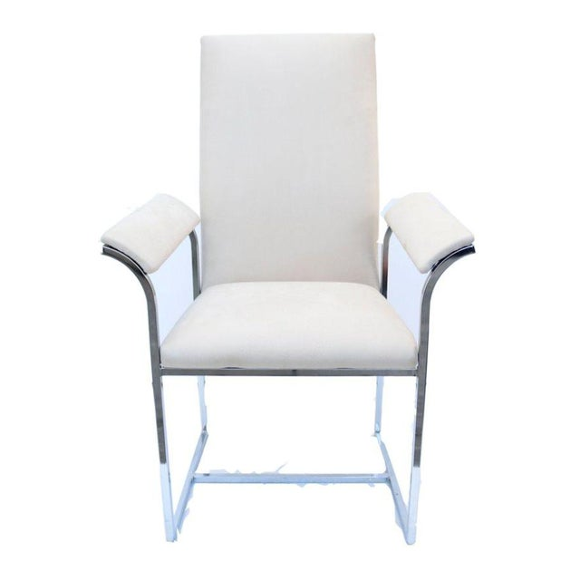 A pair of Milo Baughman chrome-framed chairs in off-white grainy leather with curved armrests.