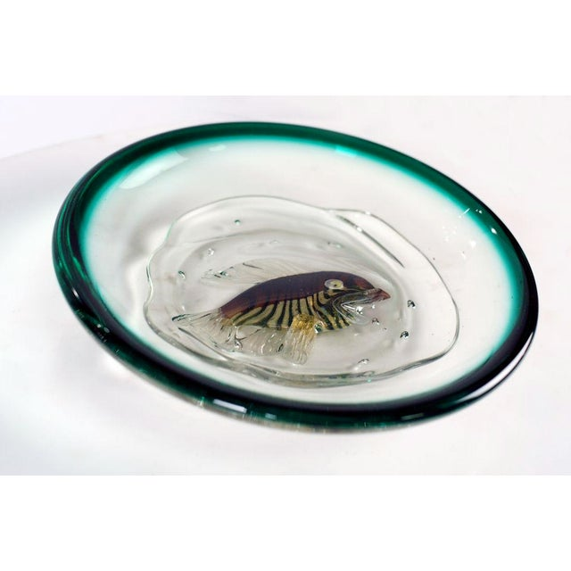A wonderful shallow dish with a dual toned rim in aquamarine and deep blue cirling a clear center with a single 'swimming'...