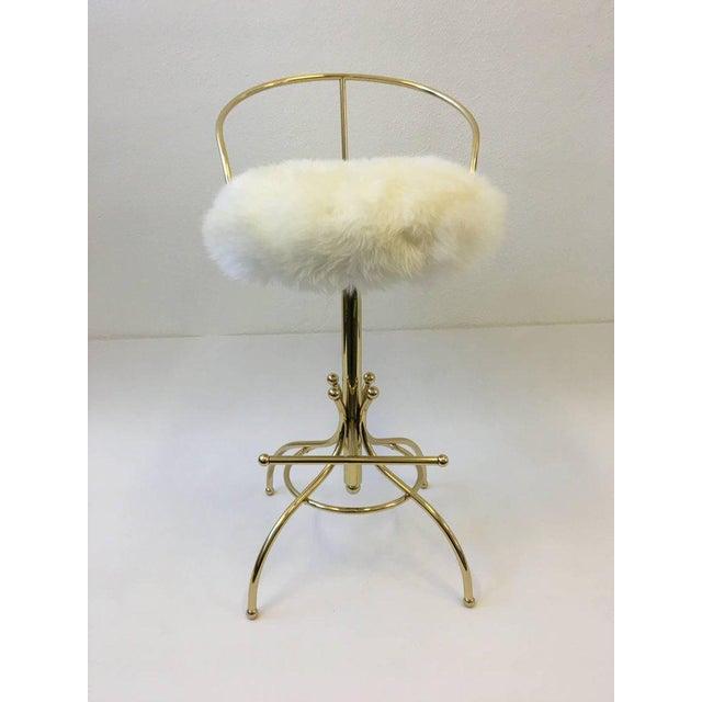A glamorous polish brass swivel Sammy Davis bar stool, part of the Ball line designed by Charles Hollis Jones for Hudson...