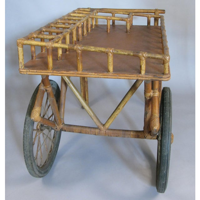 A beautiful and unusual antique 1920s rattan and wicker bar cart, with great details including large wheels with wicker...