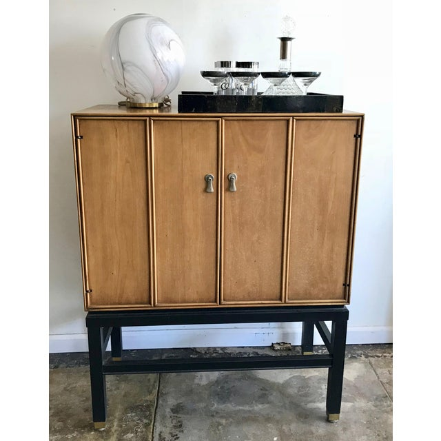 Rare mid-century oak dry bar cabinet with black lacquer wood legs and brass details. Doors open to reveal inside drawer...