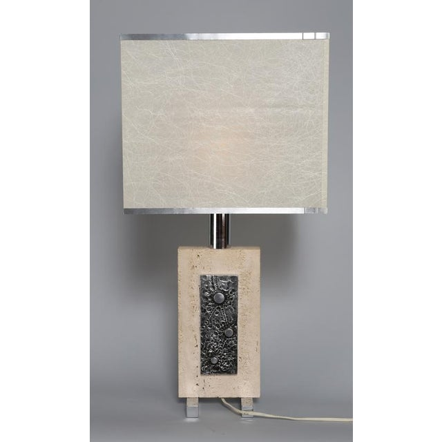 Chic 1970s lamp features travertine slab with brutalist metal plate on two steel legs. Square aluminum-trimmed shade. We...