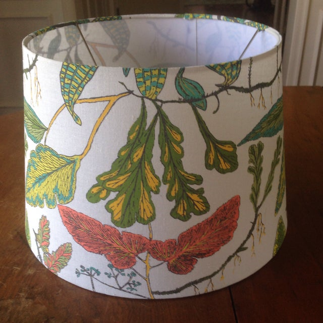 A vintage lamp shade in a bright, botanical print. Exterior is a natural fiber material over an interior, light plastic...